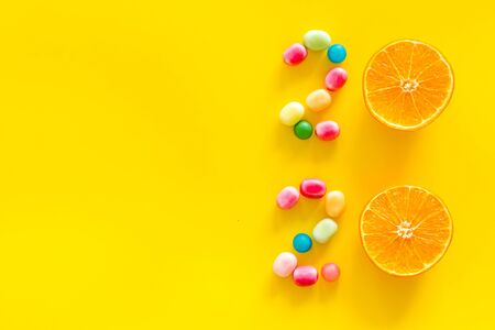 Sweet New Year design. 2020 laid out with candy and oranges on yellow background top view copy space 写真素材