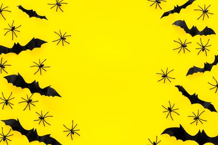 Stylish Halloween design. Bats and spiders on yellow background top view copy space frame Stock Photo
