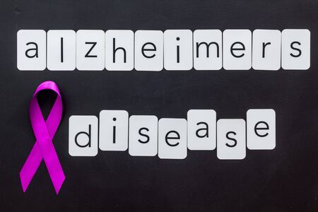 Alzheimers disease text near violet ribbon on black background top view Zdjęcie Seryjne - 131087050
