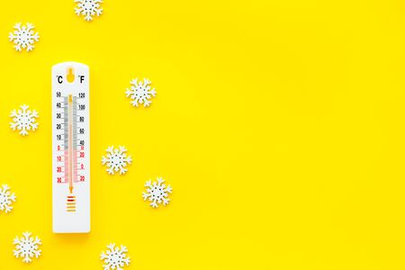 Its snowing concept. Snow and thermometer on yellow background top view copy space