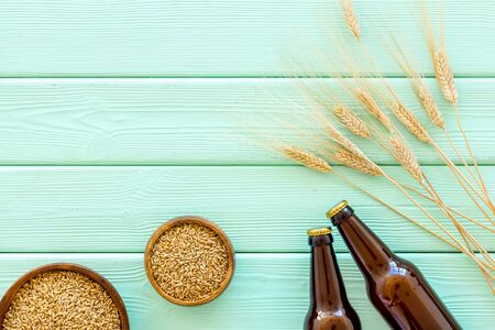 Barley or wheat as beer ingredient near beer bottles on green wooden background top view copy space