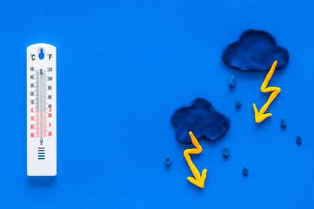 Rainy weather. Thermometer near clouds and drops on blue background top view copy space