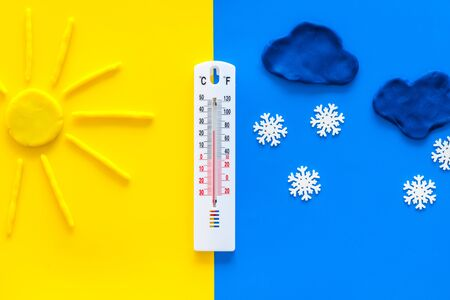 Its snowing concept. Snow and thermometer on yellow and blue background top view copy space Stock Photo