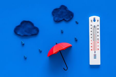 Rain concept. Weather thermometer near umbrella and drops on blue background top view Stock Photo