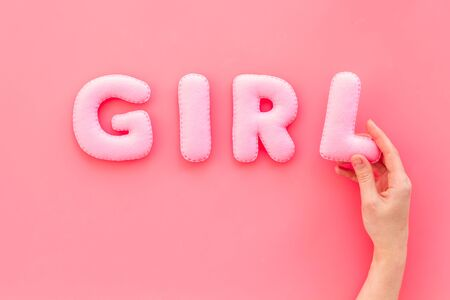 Girl word as decoration for baby shower on pink background top view copy space