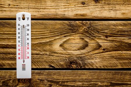 Weather thermometer on dark wooden background top view copy space