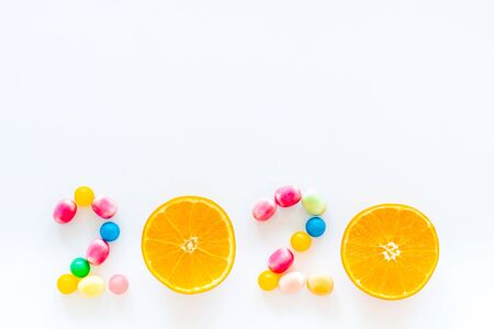 Sweet New Year design. 2020 laid out with candy and oranges on white background top view copy space 写真素材