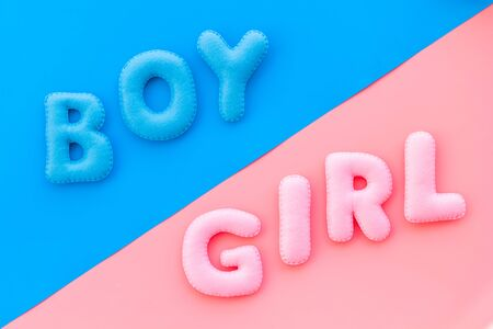 Baby shower concept. Words boy and girl on pink and blue background top view. Stock Photo