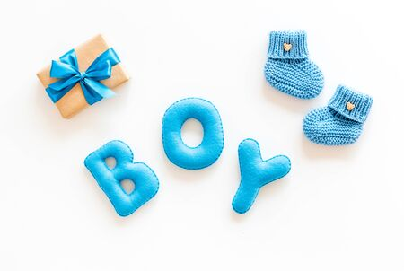 Childrens birthday concept. Word boy near booties and present box on white background top view. Stock Photo