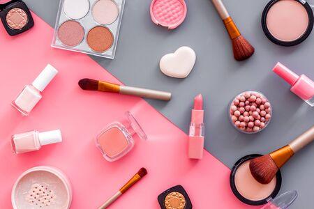 Make-up-Hintergrund mit Rouge, Puder und Werkzeugen auf rosa und grauer Tischplattenansicht.