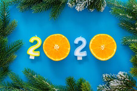 2020 New Year design. Date laid out by candles near fir branches on blue background top view 写真素材