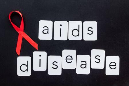 AIDS disease text near red ribbon on black background top view 版權商用圖片