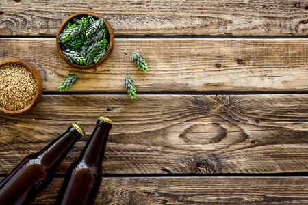 Barley and hop for making beer on rustic wooden background top view copy space
