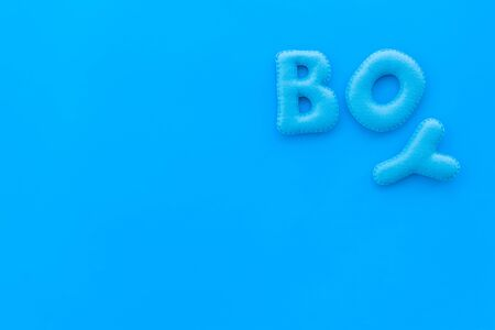 Boy word as decoration for baby shower on blue background top view frame copy space
