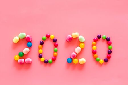 Sweet New Year design. 2020 laid out with candy on pink background top view copy space