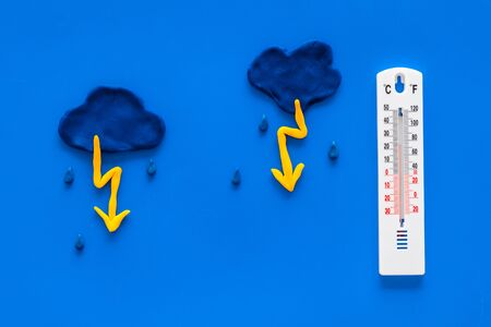 Rainy weather. Thermometer near clouds and drops on blue background top view