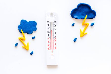 Rainy weather. Thermometer near clouds and drops on white background top view copy space