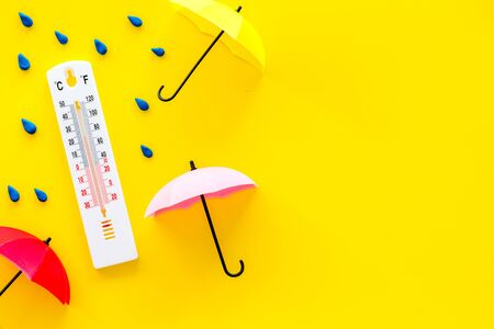 Rain concept. Weather thermometer near umbrella and drops on yellow background top view space for text