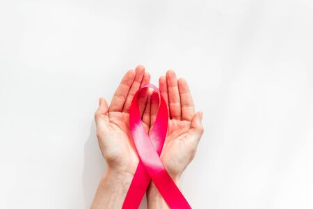 Pink ribbon in hands as symbol of breast cancer awareness on white background top view copy space Stockfoto