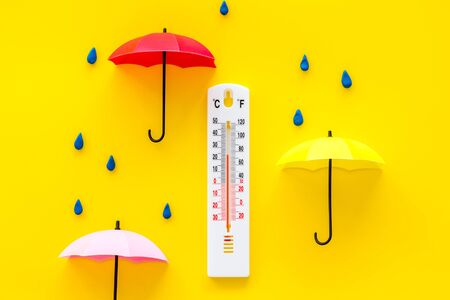 Rain concept. Weather thermometer near umbrella and drops on yellow background top view Stock Photo
