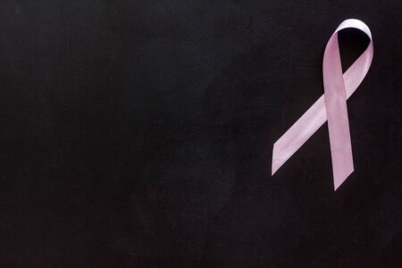 Pink ribbon as symbol of breast cancer awareness on black background top view Standard-Bild - 131303762
