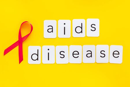 AIDS disease text near red ribbon on yellow background top view c
