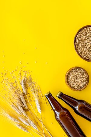 Beer ingredients. Barley near beer bottles on yellow background top view. Stock Photo