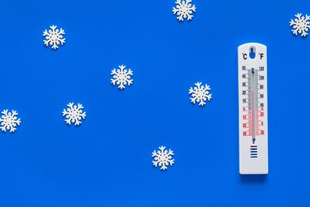 Its snowing concept. Snow and thermometer on blue background top view. Stock Photo