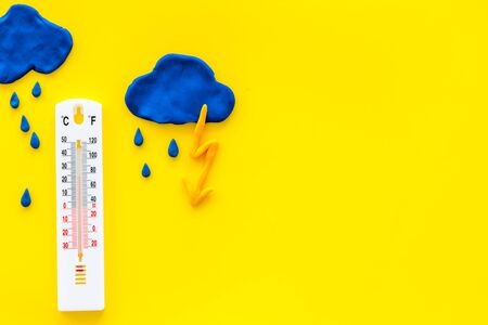 Rainy weather. Thermometer near clouds and drops on yellow background top view copy space