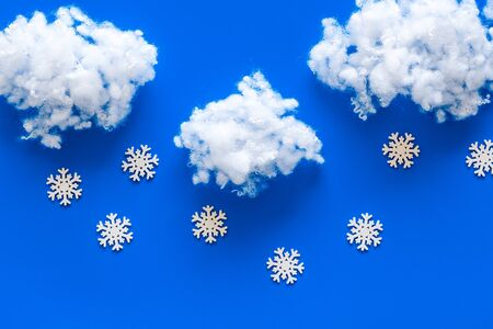 Snow and clouds on blue background top view copy space