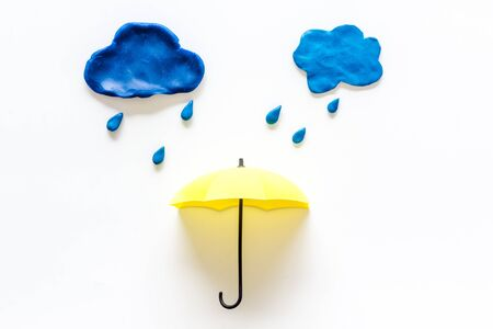 Rain concept, bad weather. Clouds and umbrella on white background top view.