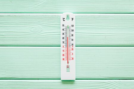 Weather thermometer on green wooden background top view. Stock Photo
