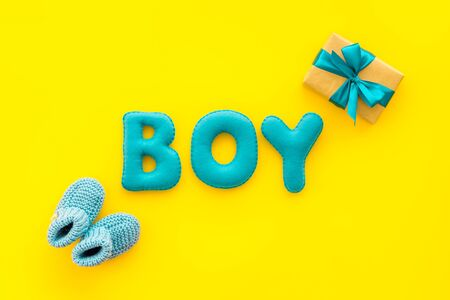 Childrens birthday concept. Word boy near booties and present box on yellow background top view.