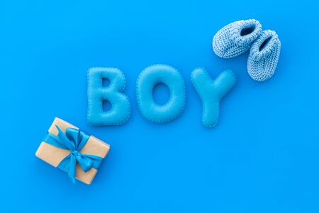 Childrens birthday concept. Word boy near booties and present box on blue background top view.