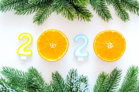 2020 New Year design. Date laid out by candles near fir branches on white background top view.