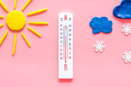 Its snowing concept. Snow and thermometer on pink background top view.