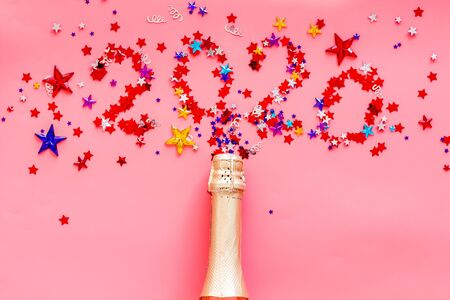 Celebrate New Year 2020. Date on confetti near champagne bottle on pink background top view.