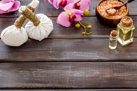 Massage thai herbal balls near spa accessories and orchids on dark wooden background copy space Stock Photo