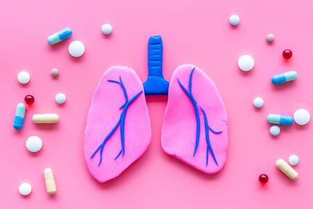 Treat lung diseases. Organ and pills on pink background top view