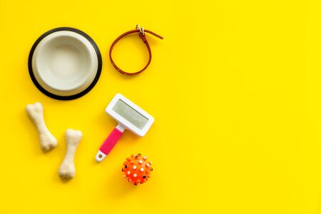 Set of treats and toys for pets with bones, collar and bowl on yellow background top view frame space for text Фото со стока