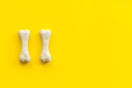 Food and toys for dogs. Chewing bones on yellow background top view space for text Фото со стока