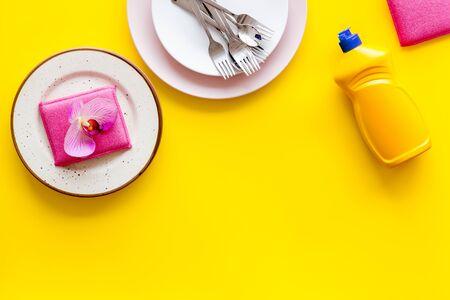 Dishwashing liquid bottle near plates on yellow background top view.