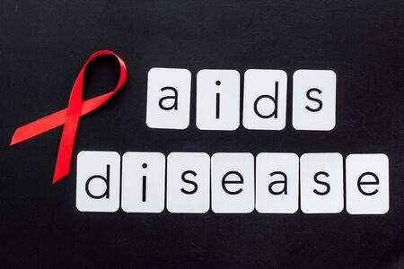 AIDS disease text near red ribbon on black background top view.