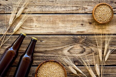 Beer background with barley on rustic wooden background top view.