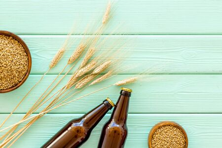 Barley or wheat as beer ingredient near beer bottles on green wooden background top view.