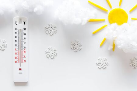 Its snowing concept. Snow and thermometer on white background top view.