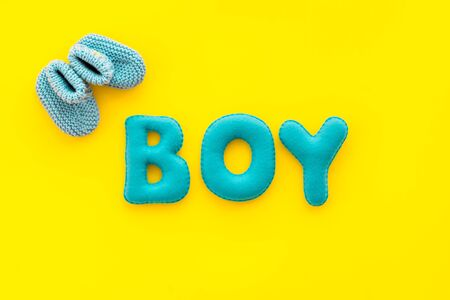 Childrens birthday concept. Word boy near booties on yellow background top view. Stock Photo
