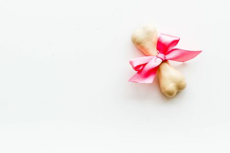 Small present for dogs. Chewing bones with bow on white background top view.