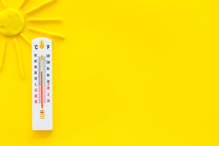 Sunny weather concept. Sun and thermometer on yellow background top view. Stock Photo