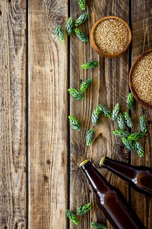 Barley and hop for making beer on rustic wooden background top view.